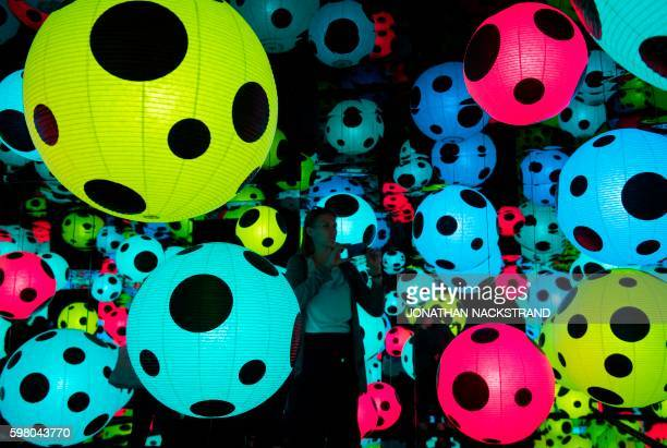 Visitors discover an art installation entitled 'Infinity Mirrored Room Hymn of Life' 2015 by Japanese artist Yayoi Kusama part of the In Infinity art...