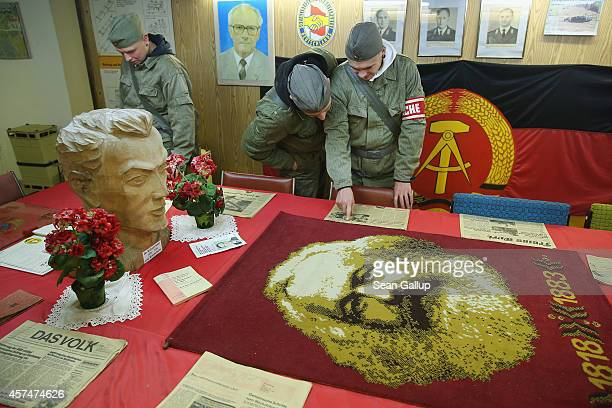 Visitors dressed as East German NVA army soldiers look at memorabilia of the former communist East Germany including old newspapers the East German...