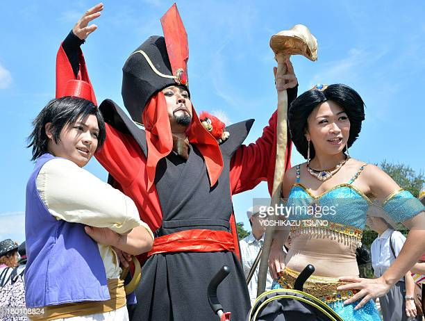 Visitors dressed in costumes from Disney's movie 'Aladdin' pose for a photo at Tokyo Disneyland in Urayasu suburban Tokyo on September 9 2013 Tokyo's...