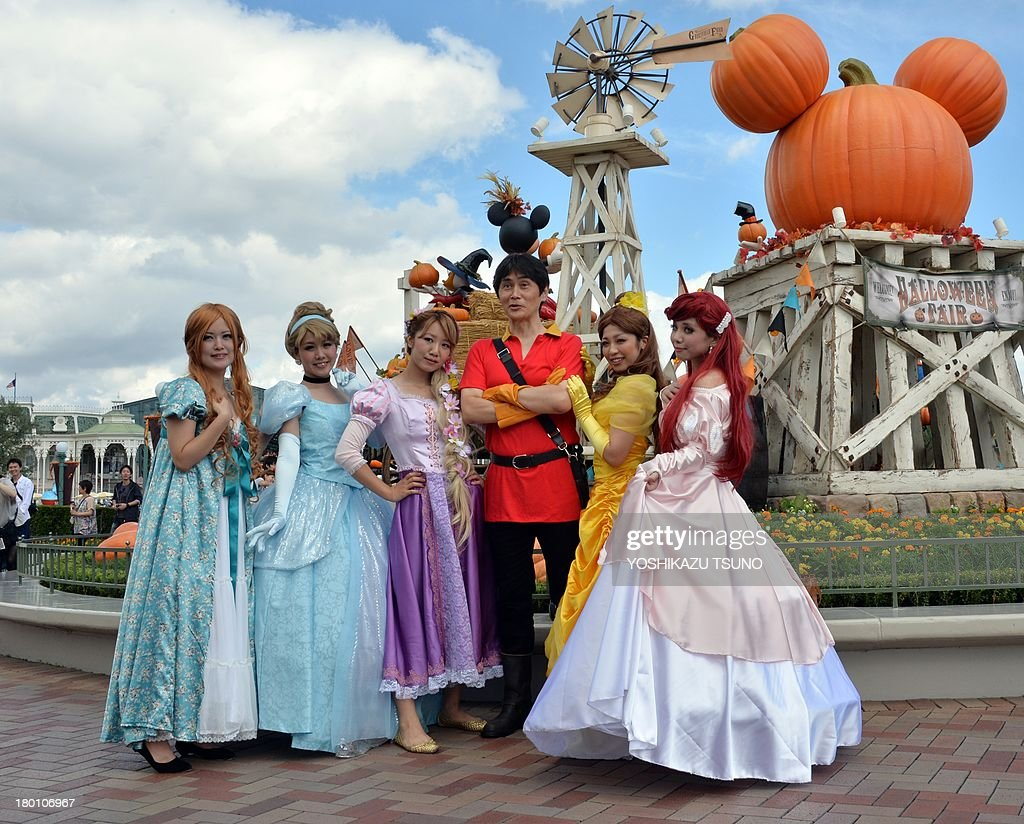 Visitors dressed in costumes of Disney princesses pose for photos at Tokyo Disneyland in Urayasu, suburban Tokyo on September 9, 2013. Tokyo's Disney theme park runs Halloween events through till October 31 and visitors are allowed to wear Disney related costumes in the park. AFP PHOTO / Yoshikazu TSUNO