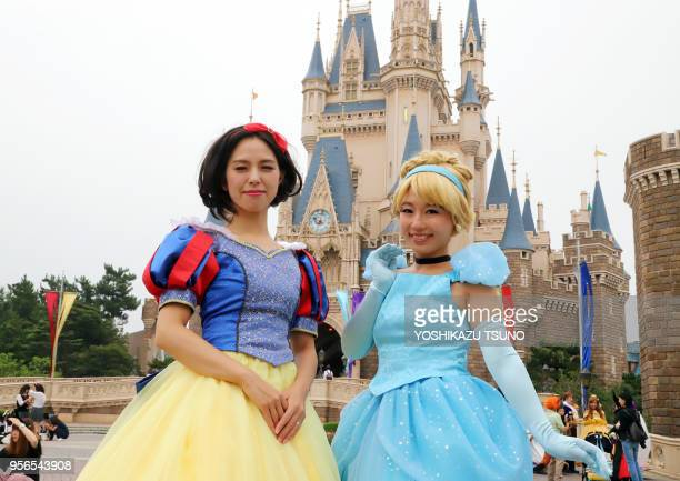 Visitors dressed in costumes of Disney's animated movie characters pose for photo at Tokyo Disneyland in Urayasu, suburban Tokyo on September 7,...