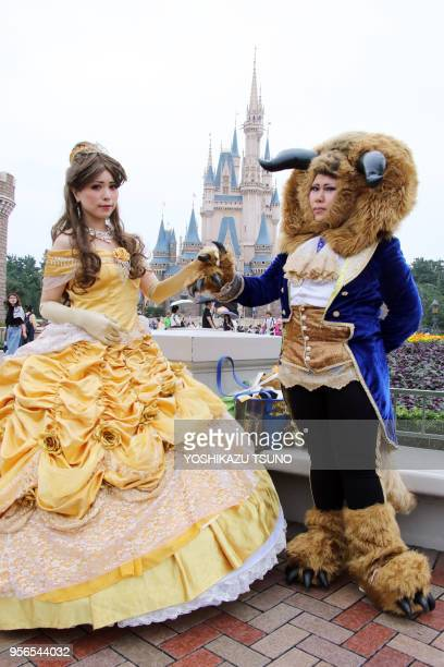 Visitors dressed in costumes of Disney's animated movie characters pose for photo at Tokyo Disneyland in Urayasu suburban Tokyo on September 7 2017...