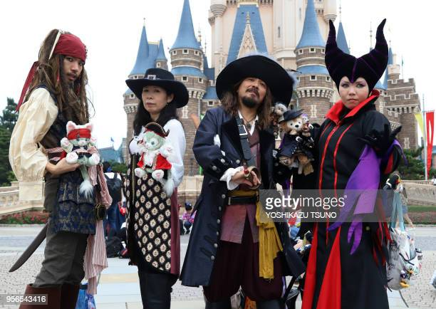 Visitors dressed in costumes of Disney's movie characters pose for photo at Tokyo Disneyland in Urayasu, suburban Tokyo on September 7, 2017. Tokyo's...