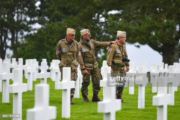 Visitors dressed in US Army 1944 uniforms view the graves of fallen soldiers at the Normandy American Cemetery that contains the remains of 9,387...