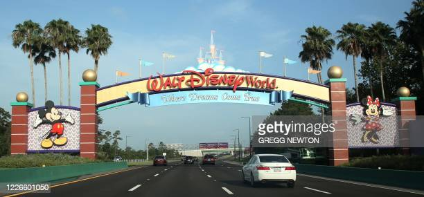 Visitors drive past a sign welcoming them to Walt Disney World on the first day of reopening of the iconic Magic Kingdom theme park in Orlando,...