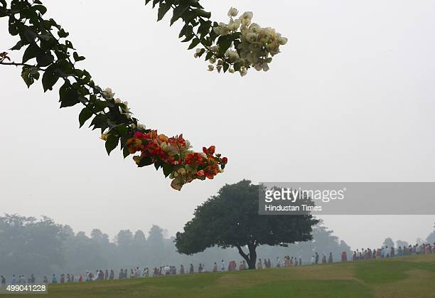 Visitors during a foggy and cold morning at Raj Ghat on November 28 2015 in New Delhi India Dense fog continued to disrupt normal life in North India...