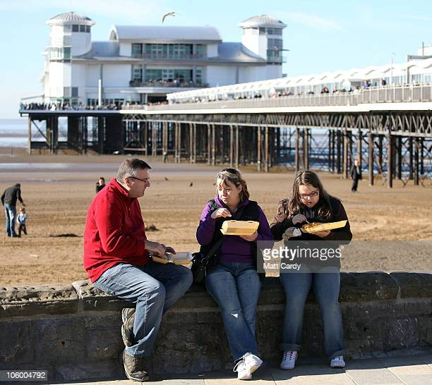 Visitors eat fish and chips in front of the the Grand Pier on October 25 2010 in WestonSuperMare England The pier which was completely destroyed by...