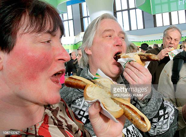 Visitors eat rostbratwurst sausages at the agriculture fair 'Green Week' at the exhibition centre in Berlin January 22 2011 Some 1200 exhibitors will...