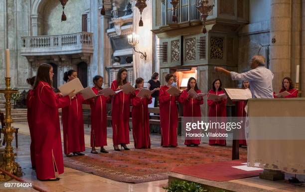 Visitors enjoy a choir performance at the Se de Lisboa the city's cathedral on June 18 2017 in Lisbon Portugal Although active all year round...
