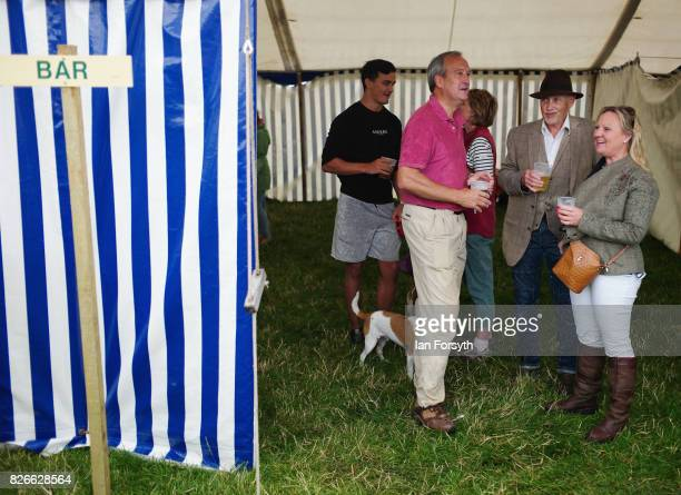Visitors enjoy a drink as they shelter from a rain shower during the Osmotherley Country Show on August 5, 2017 in Osmotherley, England. The annual...