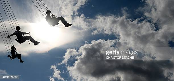 Visitors enjoy a ride on a chairoplane at the Theresienwiese fair grounds of the Oktoberfest beer festival in Munich, southern Germany, on the...