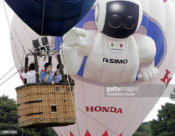 Visitors enjoy a trial flight on baord Honda's humanoid robot Asimo hot air ballon during the Balloon Festival at a Tokyo park 26 August 2007 The...