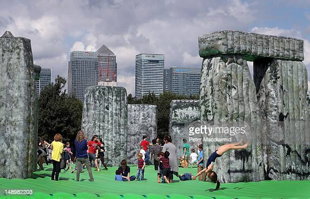 Visitors enjoy an inflatable version of Stonehenge on the Greenwich Peninsula in sight of Canary Wharf on July 21 2012 in London England The work...