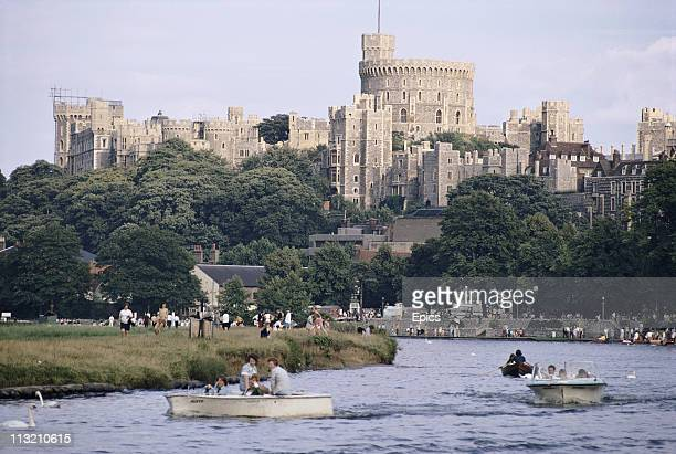 Visitors enjoy boating on the river Thames in view of Windsor Castle Berkshire England August 1970 Windsor Castle is the largest inhabited castle in...