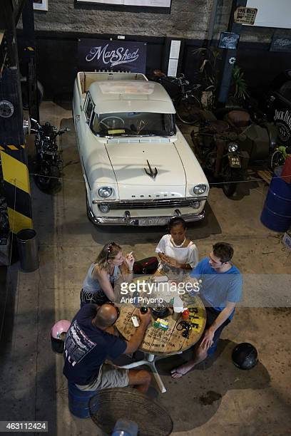 Visitors enjoy hanging out in the garage full of old motorcycles and cars in ManShed Cafe Sanur The ManShed cafe in Sanur Bali is themed on an old...