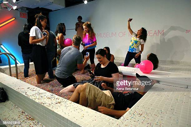 Visitors enjoy into a large pool filled with faux confetticolored sprinkles at the Museum of Ice Cream across from the Whitney Museum on July 29 2016...