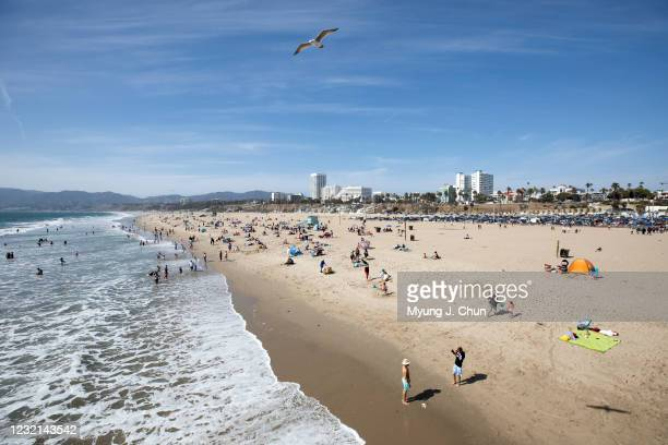 Visitors enjoy Santa Monica beach on Monday, April 5, 2021 as Los Angeles County entered the less strict orange tier allowing more places to open and...