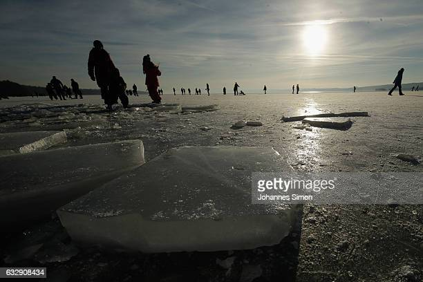 Visitors enjoy skating and walking on Lake Ammersee on January 28 2017 in Stegen am Ammersee Germany After an unusual cold winter period currently...