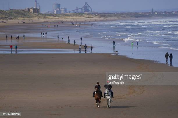 Visitors enjoy the open spaces on the beach in Saltburn By The Sea as the UK adjusts to life under the Coronavirus pandemic on March 22 2020 in...