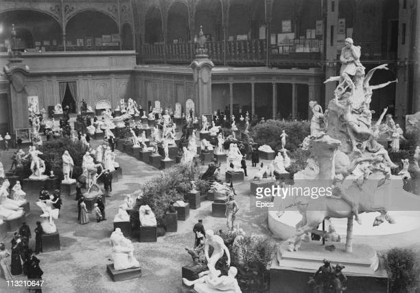 Visitors enjoy the sculptures on display in the Grand Palace at the Paris Exhibition of 1900
