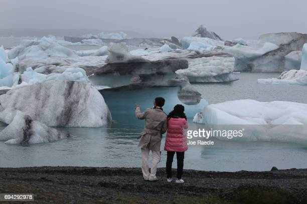 Visitors enjoy the view of Icebergs that calved from glaciers on June 3 2017 in Jokulsarlon Iceland Iceland's tourism industry continues to thrive...