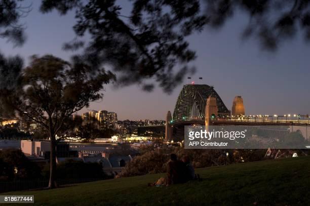Visitors enjoy the view of Sydney's iconic landmark Harbour Bridge at sunset on July 19 2017 / AFP PHOTO / SAEED KHAN