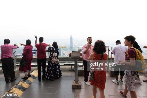 Visitors enjoy the view of the city from the KL Tower observation deck with the Tun Razak Exchange Tower in view on July 28 2018 in Kuala Lumpur...
