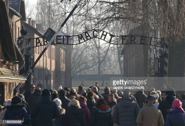 "Visitors enter through the main gate with the inscription ""Arbeit macht frei"" at the entrance to the Auschwitz German Nazi death camp ahead of German..."