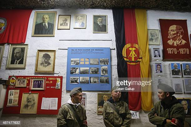 Visitors Eric Merkl Marco Schmidt and Tobias Merkl who are dressed as East German NVA army soldiers stand under memorabilia of the former communist...