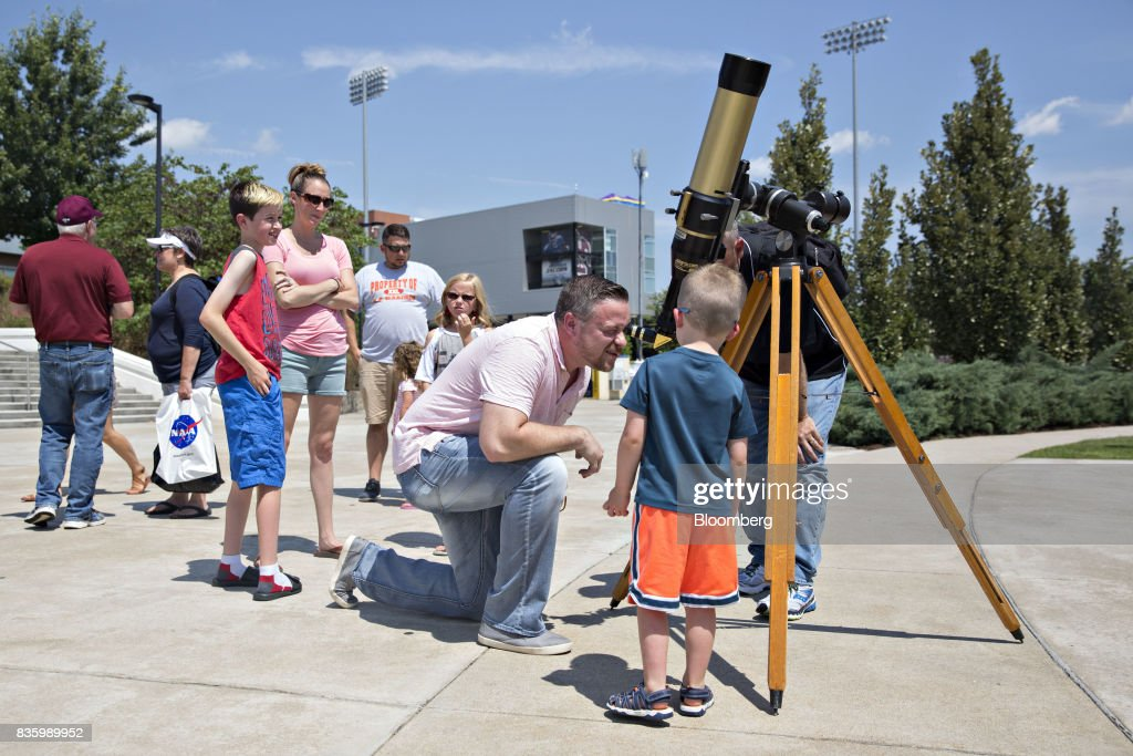 Visitors examine the sun through a telescope during an event ahead of a total solar eclipse on the campus of Southern Illinois University (SIU) in Carbondale, Illinois, U.S., on Sunday, Aug. 20, 2017. Millions of Americans across a 70-mile-wide (113-kilometer) corridor from Oregon to South Carolinawill see the sky darken as the sun disappears from view, albeit for only a few minutes at a time. Photographer: Daniel Acker/Bloomberg via Getty Images