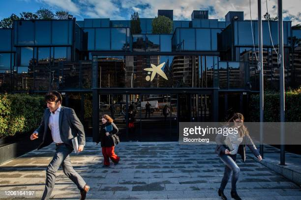 Visitors exit the headquarters of CaixaBank SA in Barcelona Spain on Thursday March 5 2020 Spanish bank shares soared after the European Unions top...