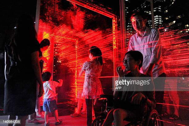 Visitors experience a light art installation made with hundreds of small laser beams titled The Gate by Chinese artist Li Hui at Singapore's Marina...
