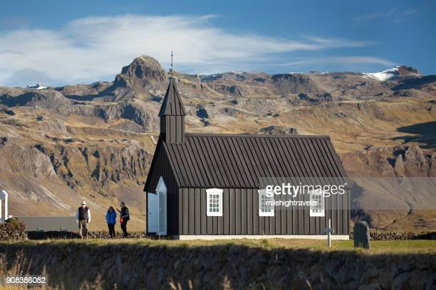 Visitors explore Iceland black church of Budir mountains Snaefellsnes Peninsula