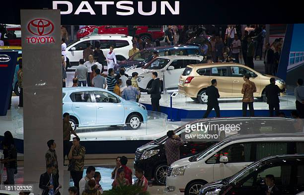 Visitors explore new cars including ones from Japanese brands Toyota and Datsun on display during the 21st Indonesia International Motor Show 2013 in...
