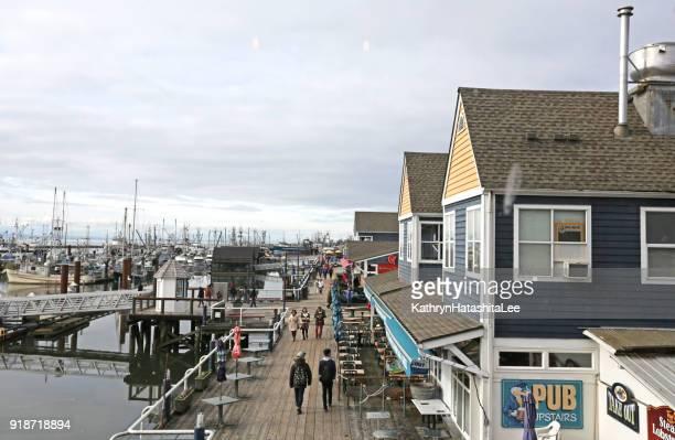 visitors explore steveston harbour, british columbia, canada - richmond british columbia stock photos and pictures
