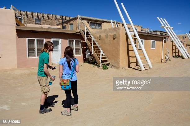 Visitors explore the stone and adobe homes at Sky City one of three Native American villages which make up Acoma Pueblo west of Albuquerque New...