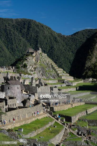 visitors file past under the intihuatana, which indicates the precise dates of solstices and equinoxes at the inca ruins of machu picchu in early morning light, unesco world heritage site, sacred valley, peru - equinozio di primavera foto e immagini stock