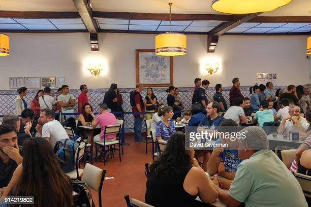 Visitors fill the famous Pastéis de Belém bakery's cafe to enjoy Pastel de nata a traditional Portuguese sweet egg pastry on October 1 2016 in the...