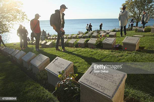 Visitors from Brisbane Australia walk among the graves of Australian Anzac soldiers killed during the Gallipoli Campaign at Beach Cemetery at Anzac...