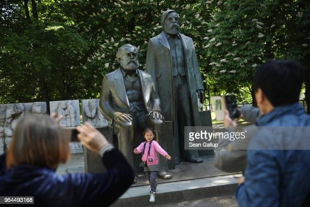 Visitors from China photograph one another in front of a statue of philosopher and revolutionary Karl Marx on May 4, 2018 in Berlin, Germany. The...