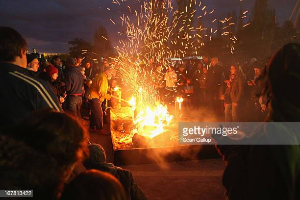 Visitors gather around a fire in Mauerpark park on Walpurgis night on April 30 2013 in Berlin Germany Walpurgis night is celebrated in many parts of...