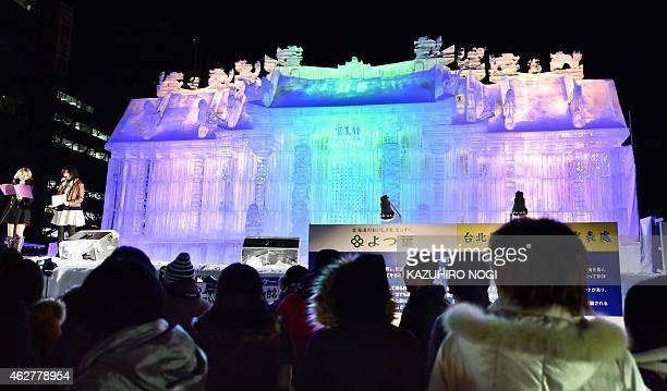 Visitors gather around a large snow sculpture of the Hsing Tian Kong a popular temple in Zhongshan Distric in Taipei during the 66th annual Sapporo...