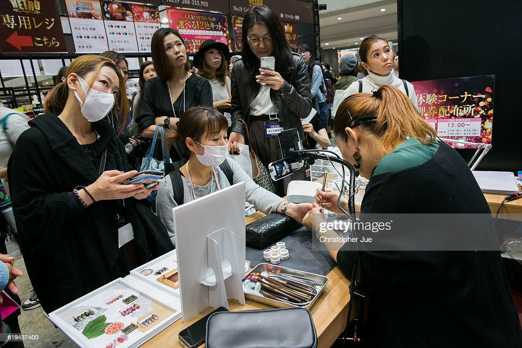 Visitors gather around a nail artist providing a demonstration on a visitor's nail during the Tokyo Nail Expo on October 31, 2016 in Tokyo, Japan. According to the organiser, approximately 50,000 people visited this 'largest nail expo in the world' held on October 30th and 31st.