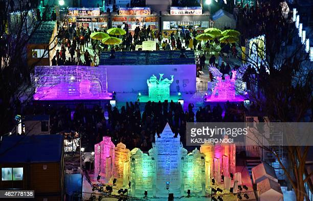 Visitors gather around colorful ice sculptures during the 66th annual Sapporo Snow Festival on February 5 2015 The weeklong festival will last until...