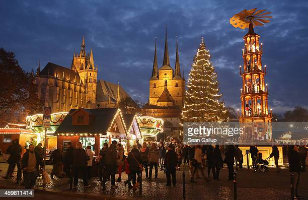 Visitors gather at the annual Christmas market on Domplatz square as the Dom cathedral and Severikirche church stand illuminated behind on November...