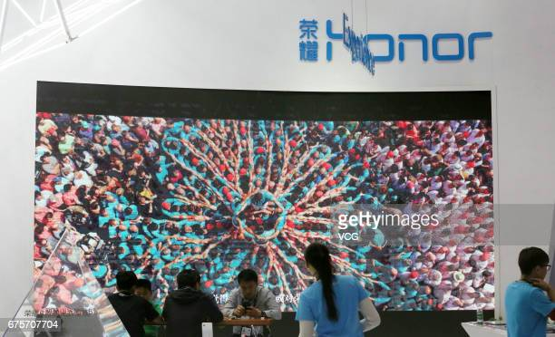 Visitors gather at the booth of Huawei Honor mobile phones during the Global Mobile Internet Conference 2017 at China National Convention Center on...