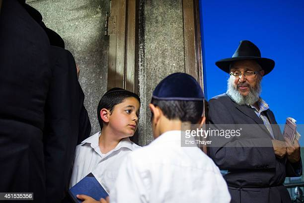 Visitors gather at the gravesite of the Lubavitcher Rebbe Rabbi Menachem Mendel Schneerson June 30 2014 at the Old Montefiore Cemetery in the Queens...