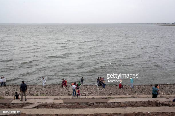 Visitors gather at the water's edge at the Jayakwadi Dam in Paithan Maharashtra India on Friday Aug 17 2018 Modi is seeking to spend more on the...