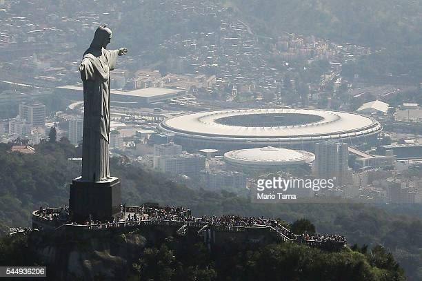 Visitors gather beneath the Christ the Redeemer statue as Maracana stadium site of the Olympic opening ceremonies stands in the background on July 4...