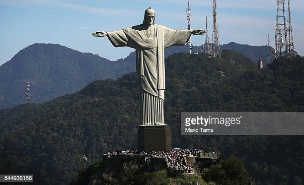 Visitors gather beneath the Christ the Redeemer statue on July 4 2016 in Rio de Janeiro Brazil July 5 marks the onemonth mark to the beginning of the...